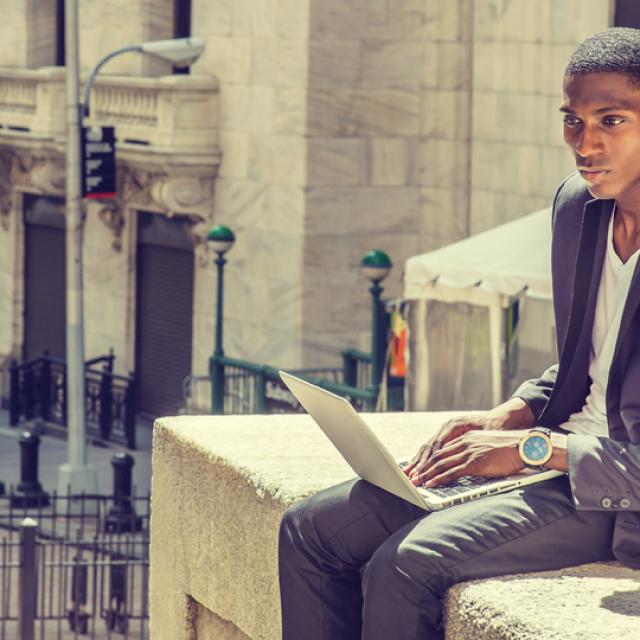Black Man on Laptop Reviewing Stocks